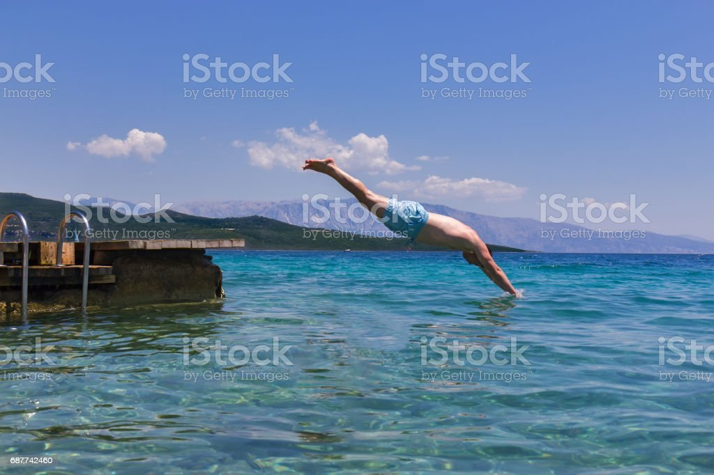Swimmer jumping to sea water stock photo