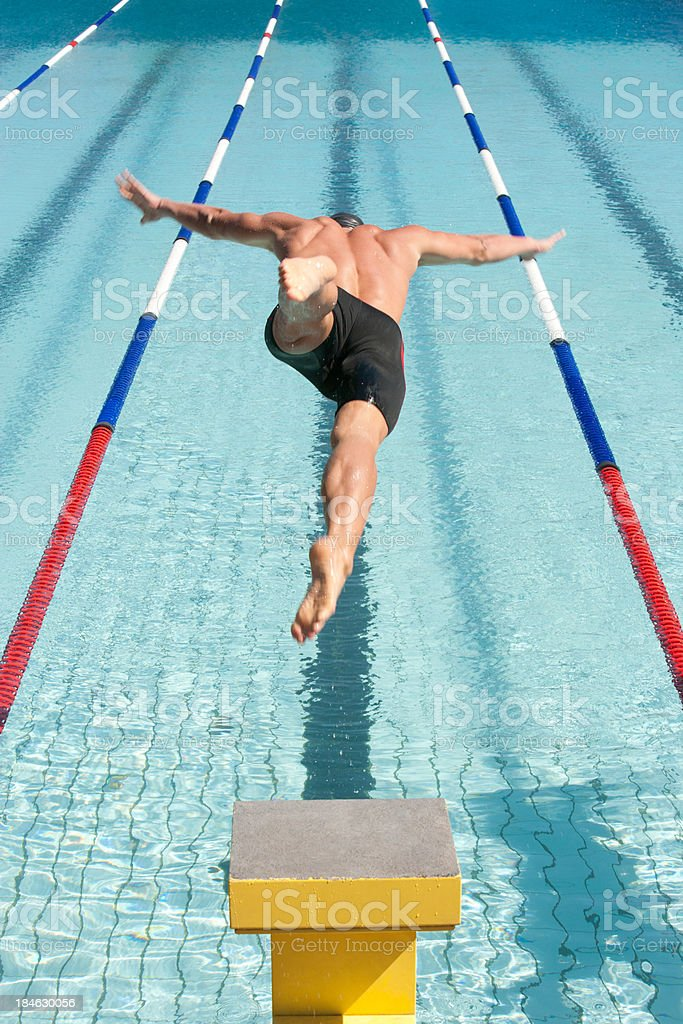 Swimmer on pool start block stock photo