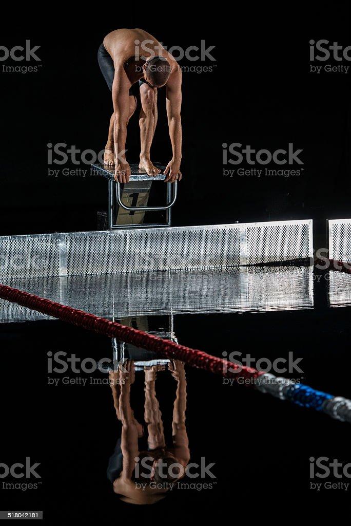 Swimmer Preparing To Jump Off The Starting Block stock photo