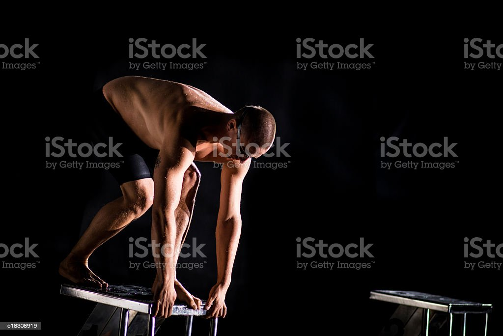Swimmer Preparing To Jump Off The Starting Block stock photo
