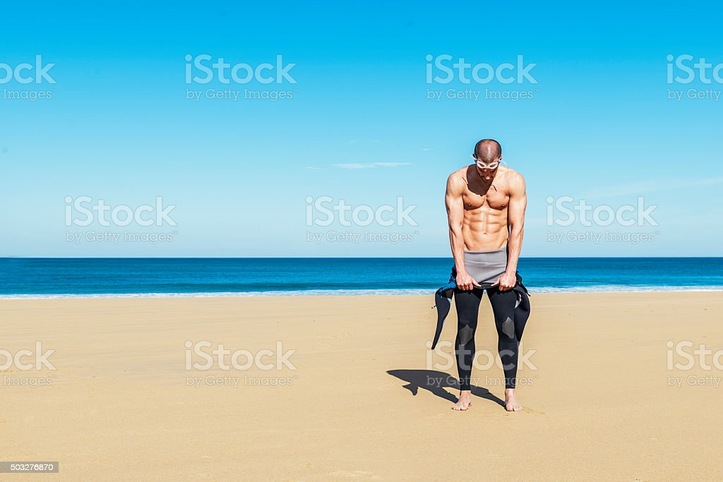 swimmer putting on his wetsuit stock photo