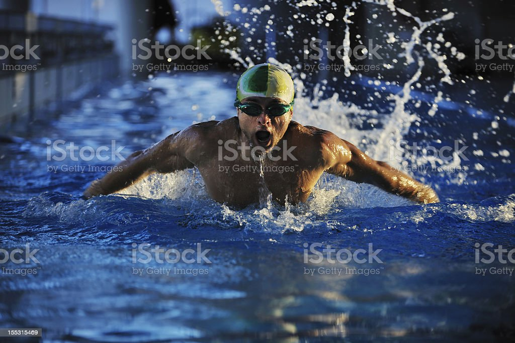 A swimmer with cap and goggles coming up out of water stock photo