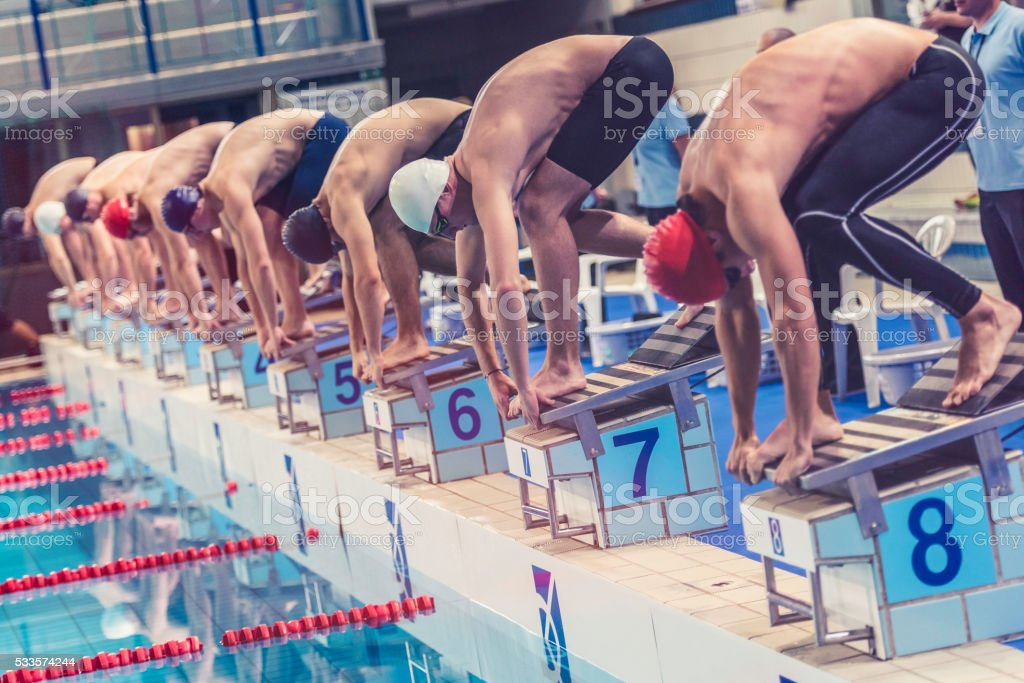 Swimmers crouching on starting block ready to jump stock photo
