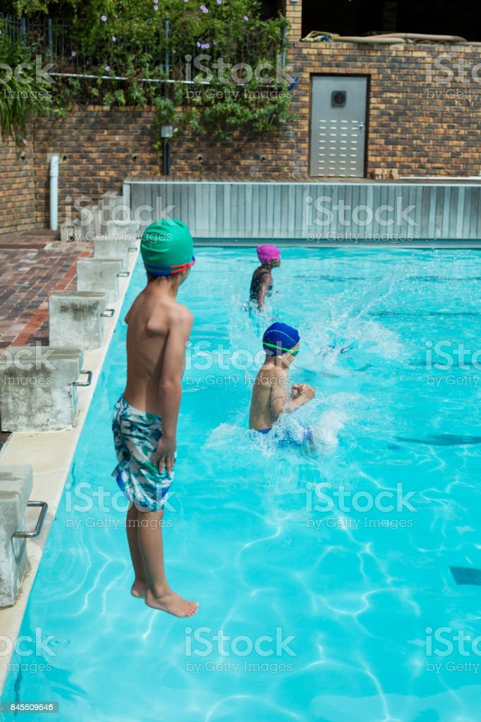 Swimmers jumping in swimming pool at leisure center stock photo