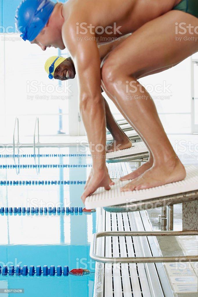 Swimmers on starting blocks stock photo