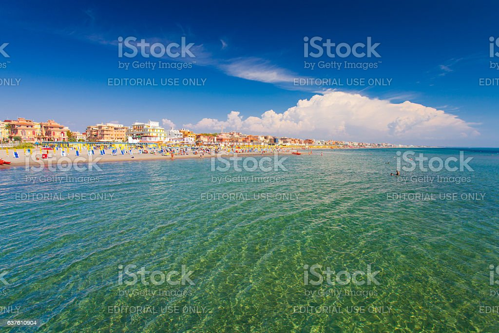 Swimming and relaxing people on the beach.Italy. stock photo