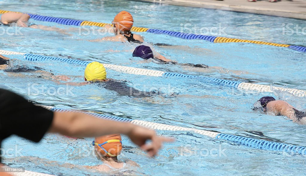 A man pointing into the pool during a swimming competition