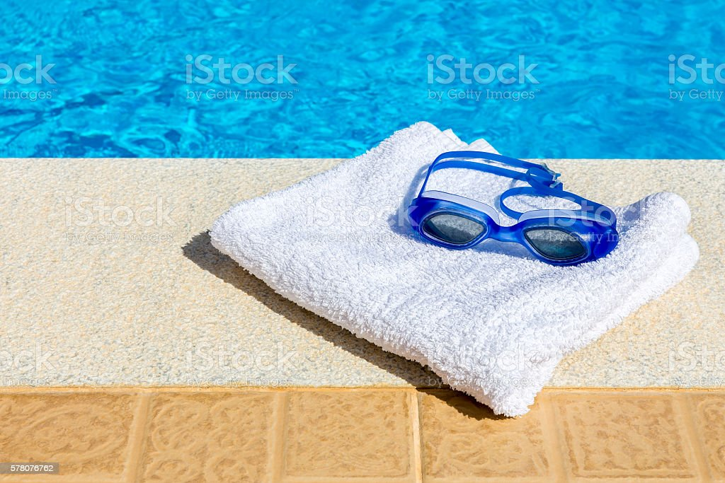 Swimming goggles and towel near swimming pool stock photo