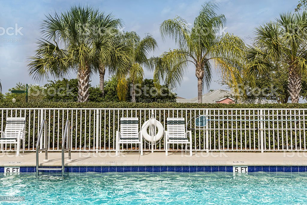 Swimming pool against palms in royalty-free stock photo