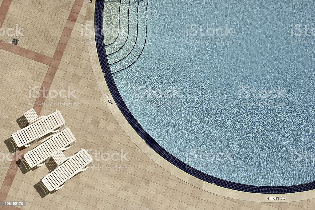 Swimming pool and lounge chairs stock photo
