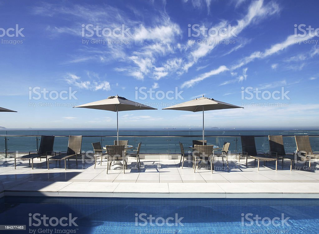 Swimming Pool and Loungers on Hotel Roof Deck stock photo