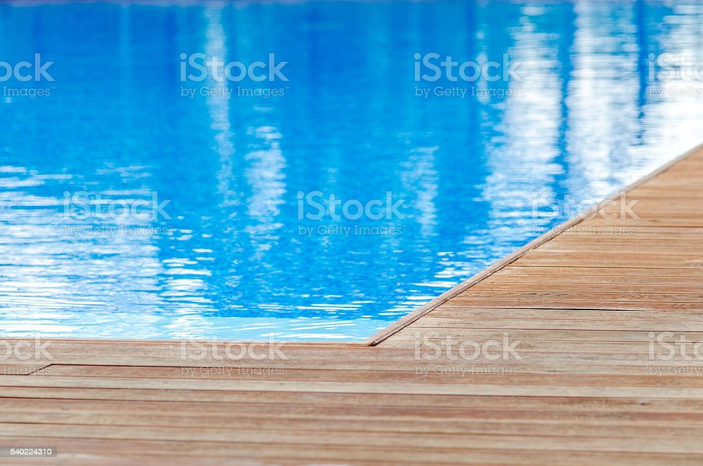 Swimming pool and wooden deck stock photo