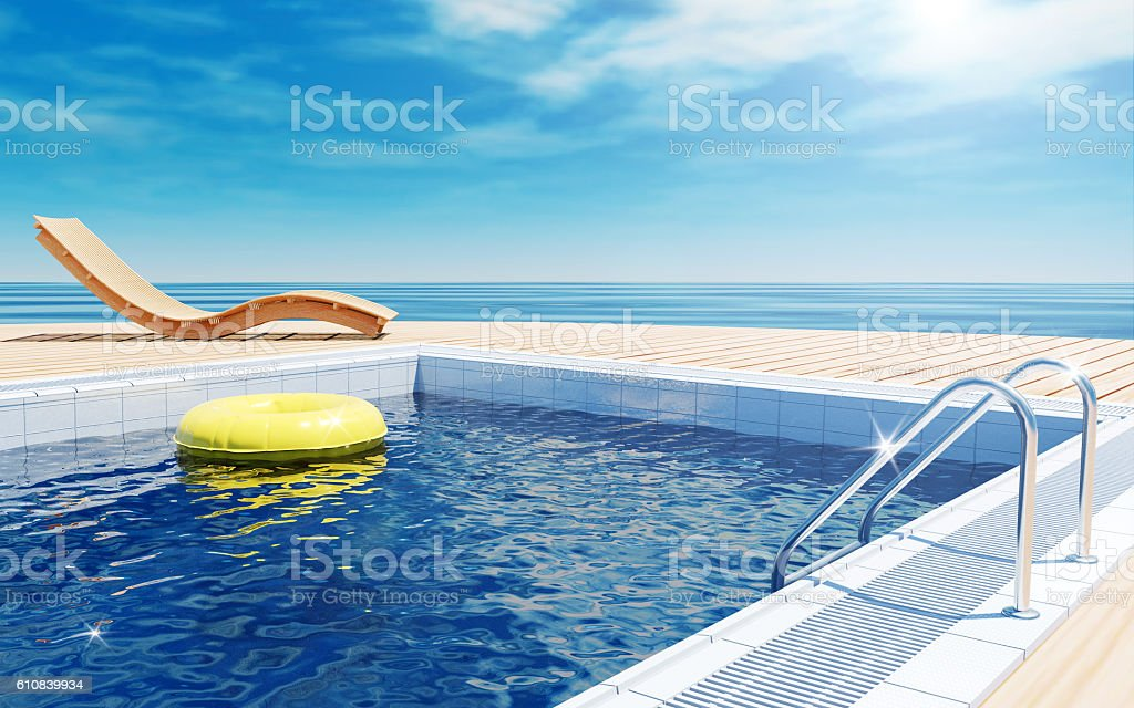 Swimming pool beach lounger on sun deck with sea view stock photo