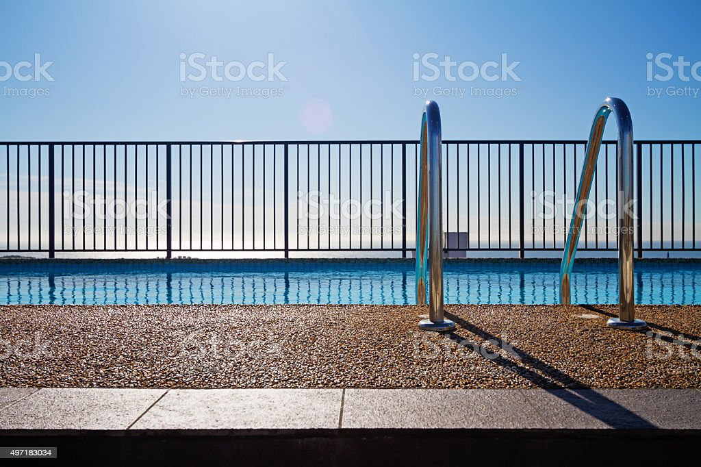 Swimming pool edge with ladder and sky background stock photo
