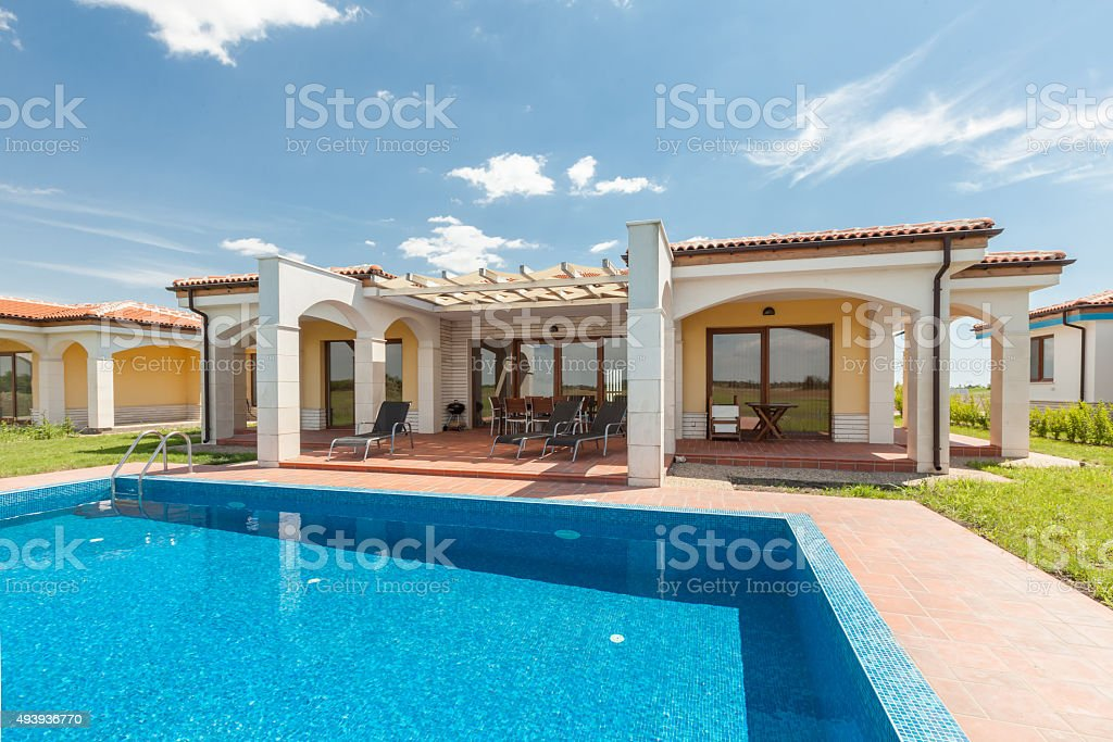 swimming pool outside luxury home stock photo
