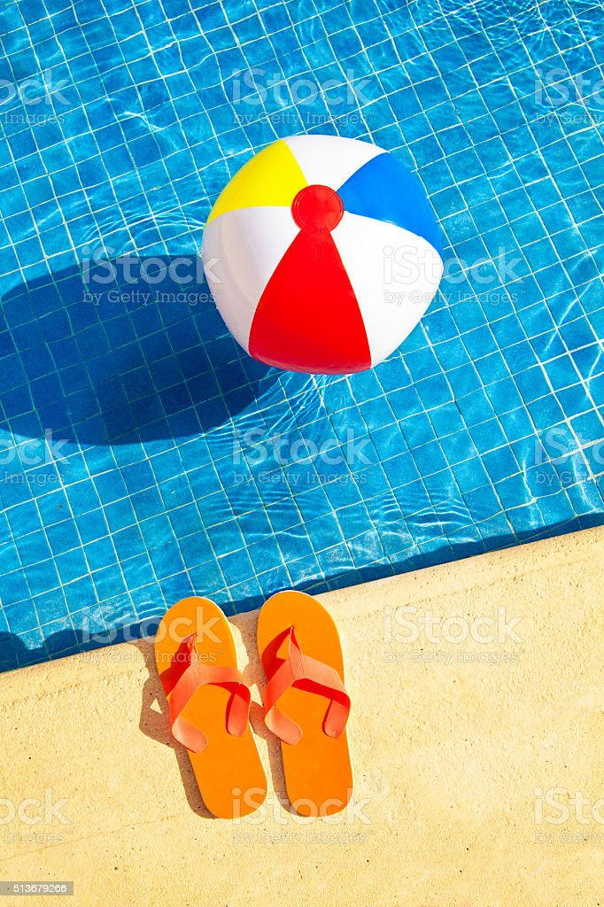 Swimming Pool Summer Fun with Floating Beach Ball, Flip Flops stock photo