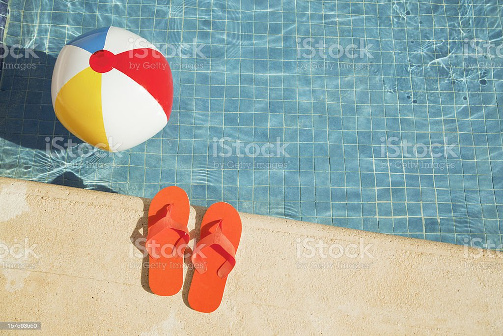 Swimming Pool Summer Vacation Fun with Floating Beach Ball, Sandals stock photo