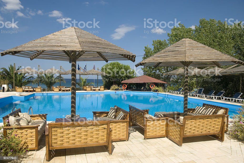 A swimming pool surrounded by chairs at a tropical resort royalty-free stock photo