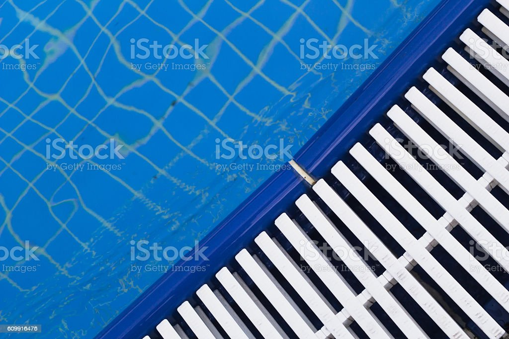 Swimming pool white grating (grille) with clear blue water and stock photo
