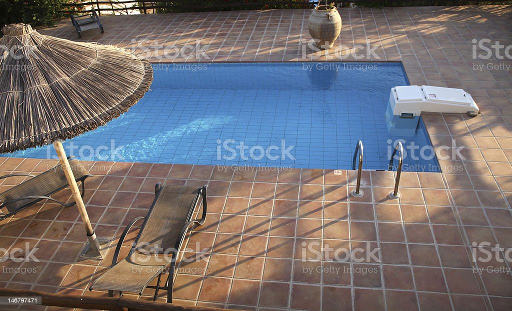 Swimming pool with deckchairs stock photo