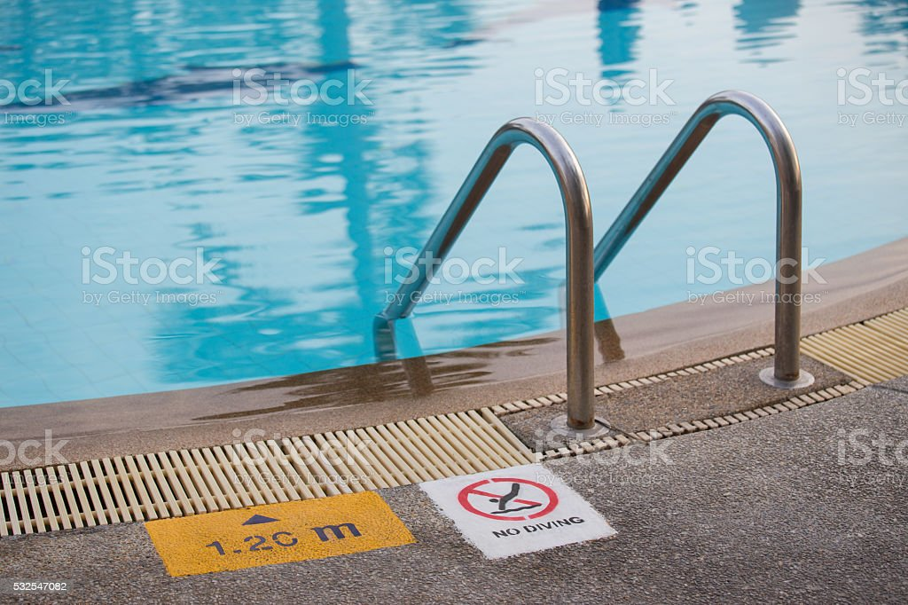 swimming pool with  ladder and sign stock photo