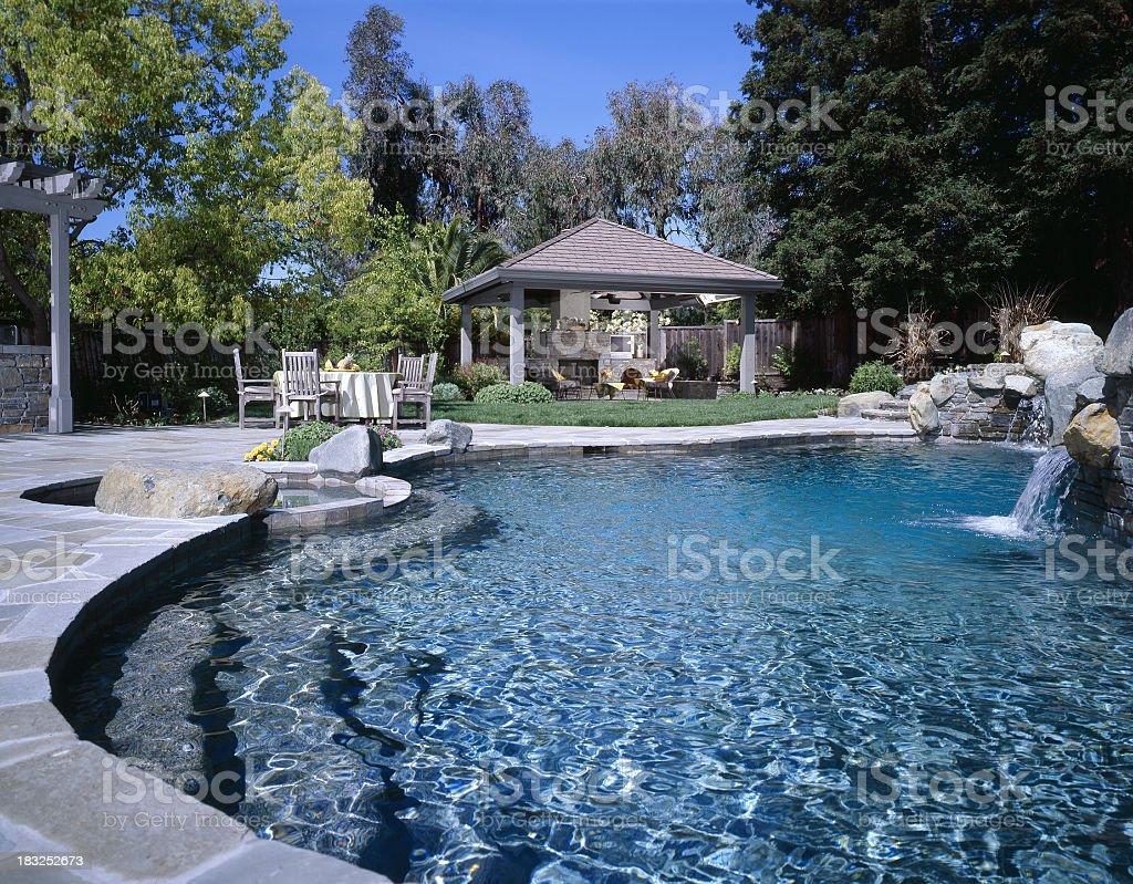 Swimming pool with waterfall in backyard royalty-free stock photo