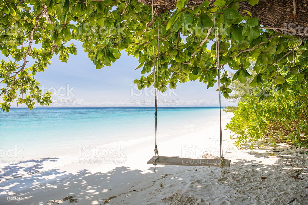 Swing on beautiful crystal clear sea and white sand beach stock photo