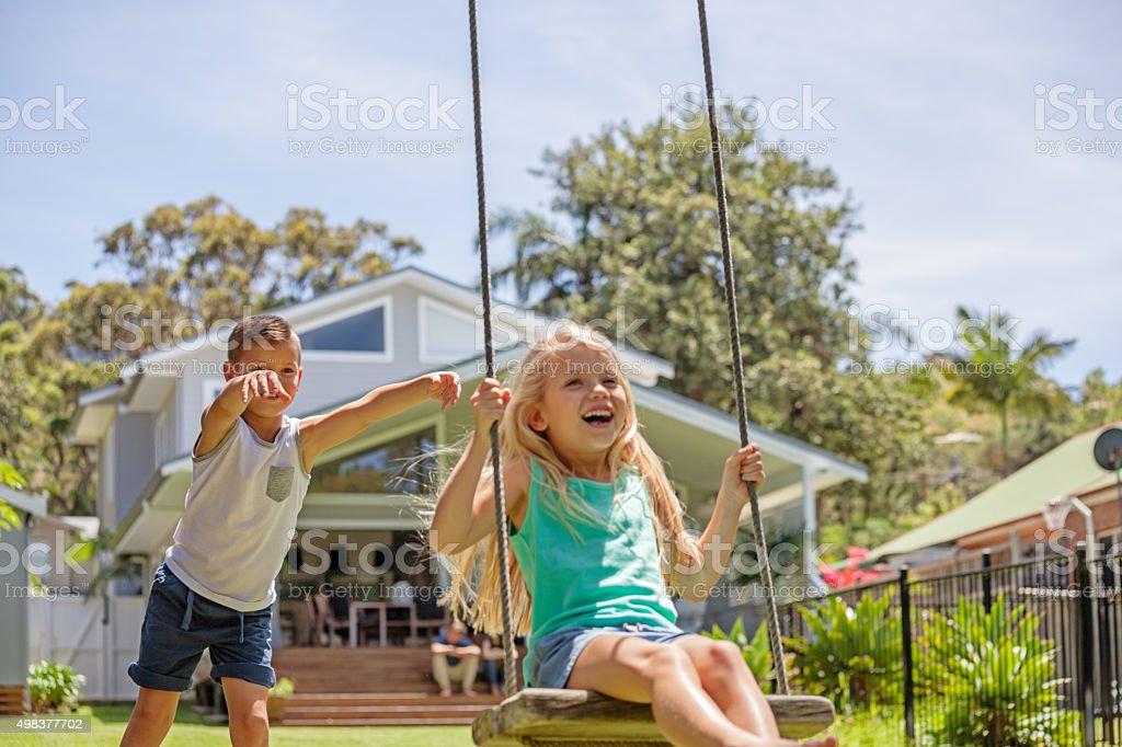 swinging in the backyard tree swing stock photo
