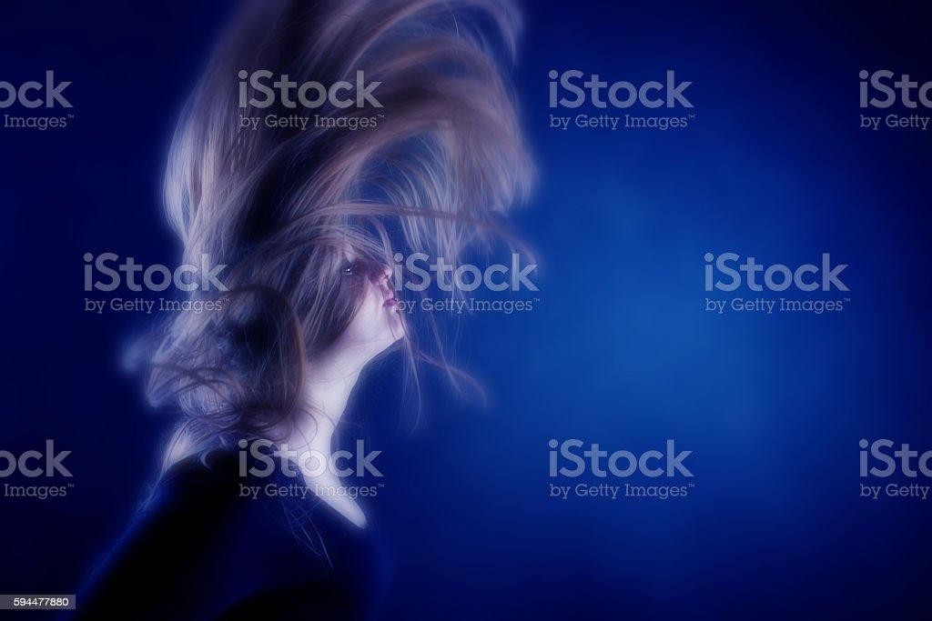 Swinging long hair on blue background. stock photo