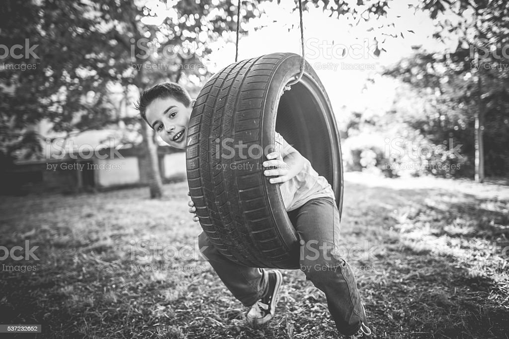 Swinging on a tire swing. stock photo