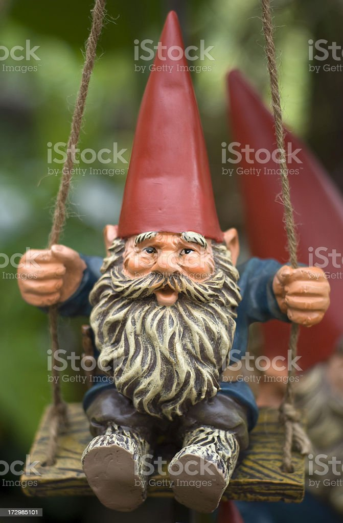 Swinging Ornamental Garden Feature, Cheerful Gnome on Swing stock photo
