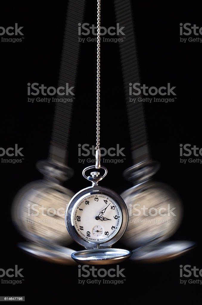 Swinging pocket watch hypnosis on black stock photo