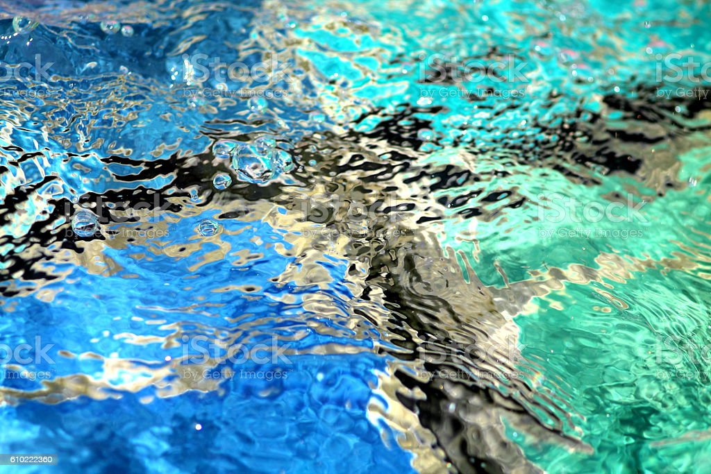 Swirling water over the cyan blue ceramic tiles stock photo