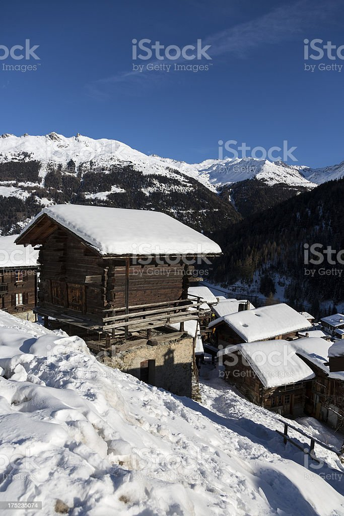 Swiss alpine Chalet and Village covered in snow royalty-free stock photo