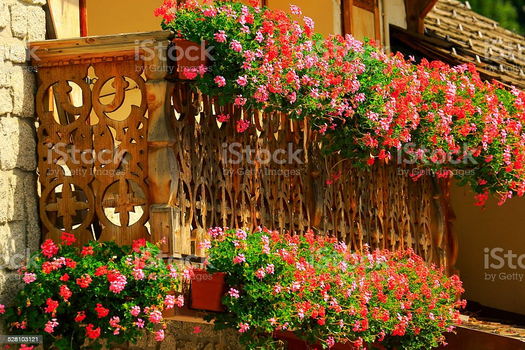 Swiss Alpine chalet - rustic mountain hut balcony and flowers stock photo