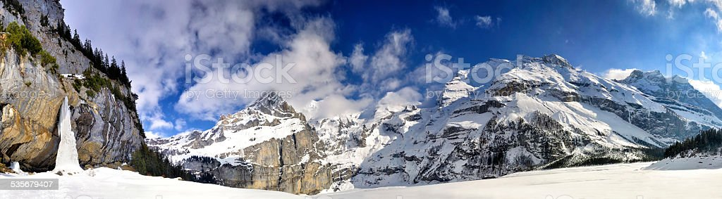 Swiss Alps Panorama with frozen waterfall stock photo