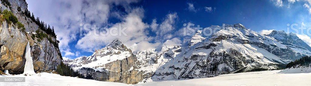 Swiss Alps Panorama with frozen waterfall stock photo