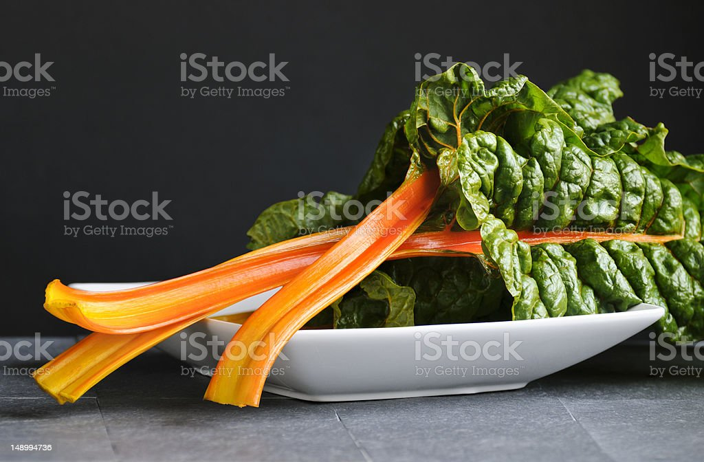 Swiss chard leaves in a white bowl stock photo