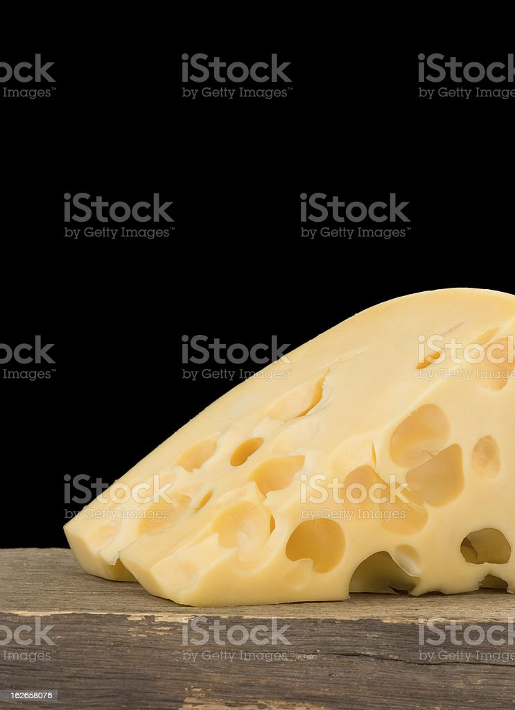 swiss cheese isolated on black at wood royalty-free stock photo