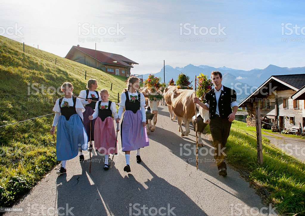 Swiss farmer family in traditional clothing walking down mountain stock photo