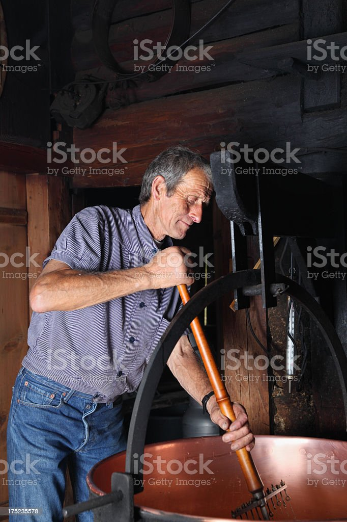 swiss farmer making traditional cheese in farm house stock photo