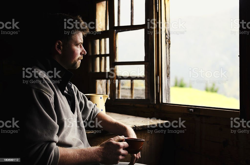 Swiss farmer staring out of window stock photo