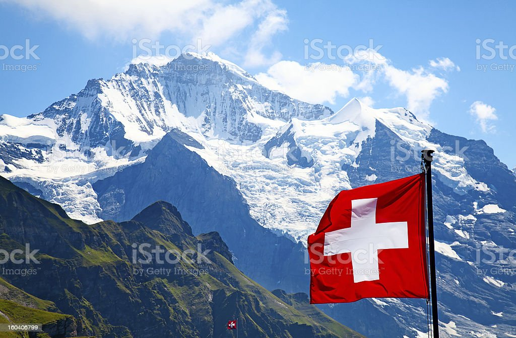 Swiss flag atop a mountain with grass and snow royalty-free stock photo