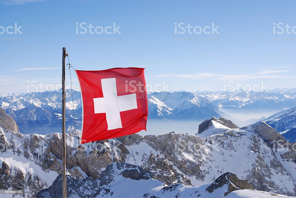 Swiss flag flying over snowy mountains royalty-free stock photo