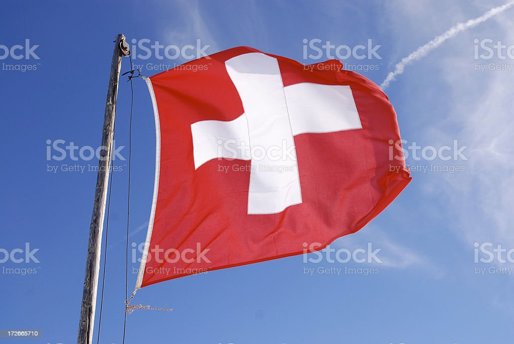 swiss flag in the wind against blue sky royalty-free stock photo