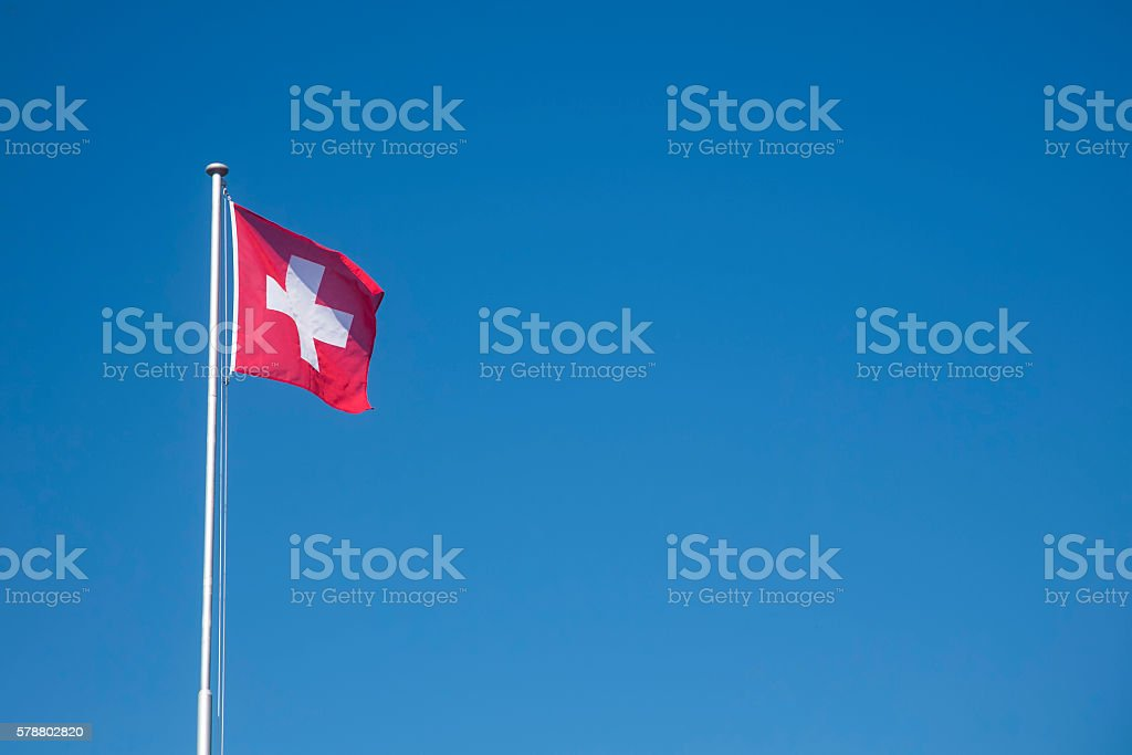 Swiss flag in wind in front of blue sky stock photo