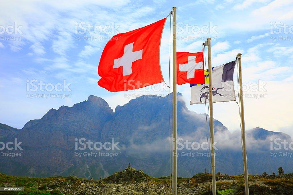 Swiss flag, Inukshuks, Graubunden flag winding at San Bernardino Pass, Swiss Alps stock photo