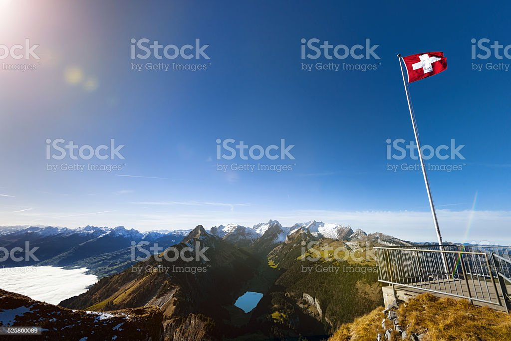 Swiss flag on Mountain Hoher Kastern over Alpstein in Appenzellerland stock photo