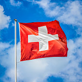 Swiss flag waving in the wind against blue sky