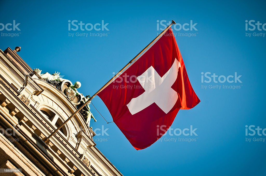 swiss flag waving on historic building royalty-free stock photo